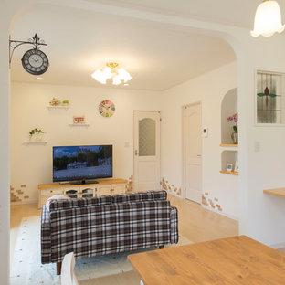 他の地域の地中海スタイルのおしゃれなリビング (白い壁、淡色無垢フローリング、据え置き型テレビ、茶色い床) の写真