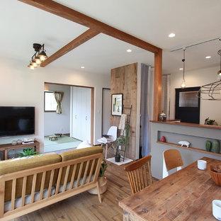 他の地域の小さいラスティックスタイルのおしゃれなLDK (白い壁、無垢フローリング、壁掛け型テレビ、茶色い床) の写真