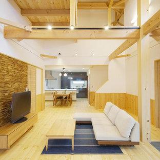 Esempio di un grande soggiorno etnico aperto con pareti bianche, pavimento in legno massello medio, TV autoportante e pavimento beige