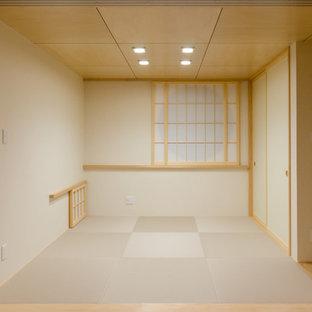Modelo de salón abierto, asiático, pequeño, con paredes beige, tatami, televisor colgado en la pared y suelo beige