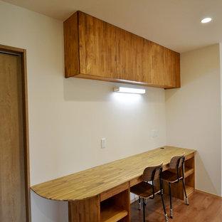 Kleines, Offenes Asiatisches Wohnzimmer mit weißer Wandfarbe, Sperrholzboden, Wand-TV und beigem Boden in Sonstige