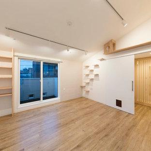 Cette image montre un salon nordique de taille moyenne et ouvert avec un mur beige, un sol en bois clair, un sol beige, un plafond voûté et un mur en parement de brique.