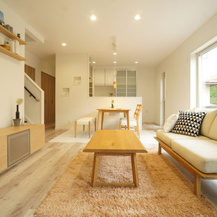 На фото: маленькая открытая гостиная комната в скандинавском стиле с белыми стенами, полом из фанеры и белым полом с