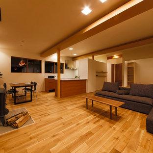 横浜の広いモダンスタイルのおしゃれなLDK (白い壁、無垢フローリング、薪ストーブ、タイルの暖炉まわり、茶色い床) の写真
