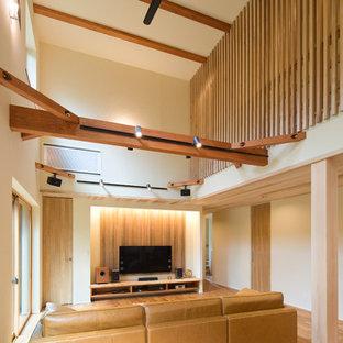 Diseño de salón abierto, minimalista, grande, con paredes blancas, suelo de madera en tonos medios y televisor colgado en la pared