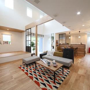 他の地域の大きいインダストリアルスタイルのおしゃれなLDK (白い壁、無垢フローリング、据え置き型テレビ、茶色い床) の写真