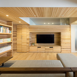 Design ideas for an asian open concept living room in Tokyo with a library, beige walls, light hardwood floors, a built-in media wall and beige floor.