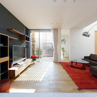 Modelo de salón abierto, asiático, de tamaño medio, con paredes negras, suelo de madera en tonos medios, televisor independiente y suelo marrón