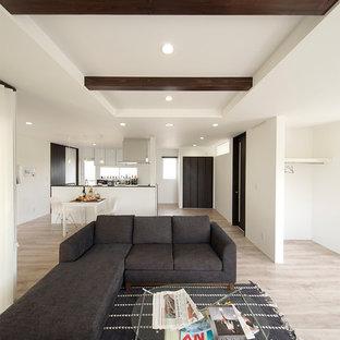 Cette image montre un salon minimaliste avec un mur blanc, un sol en contreplaqué, aucune cheminée, un téléviseur indépendant et un sol beige.
