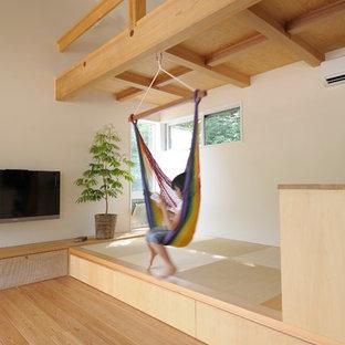 Foto di un soggiorno nordico aperto con pareti bianche, pavimento in tatami, TV a parete e pavimento verde