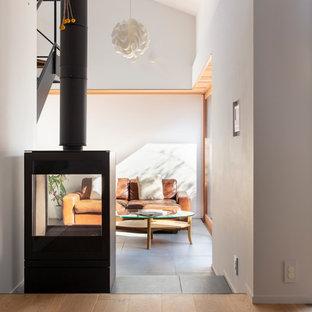 東京23区のコンテンポラリースタイルのおしゃれなリビング (グレーの壁、両方向型暖炉、金属の暖炉まわり、グレーの床、無垢フローリング) の写真