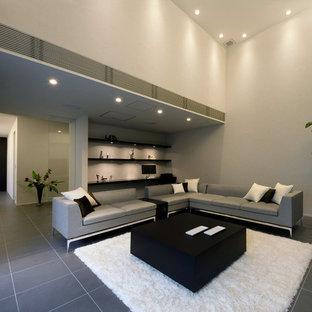 Immagine di un grande soggiorno minimalista chiuso con sala formale, pareti grigie, pavimento in ardesia, nessun camino e TV autoportante