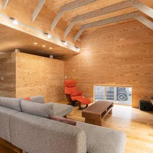 他の地域のアジアンスタイルのおしゃれなLDK (茶色い壁、無垢フローリング、壁掛け型テレビ、茶色い床) の写真