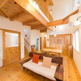 Esempio di un soggiorno etnico con pareti bianche, pavimento in legno massello medio e pavimento marrone