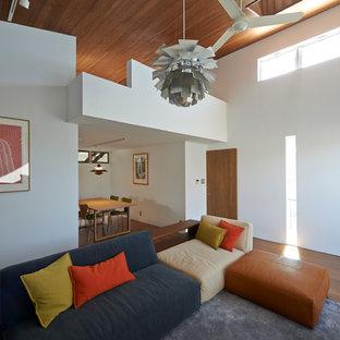 Foto di un soggiorno di medie dimensioni e stile loft con pareti bianche, pavimento in compensato e TV a parete