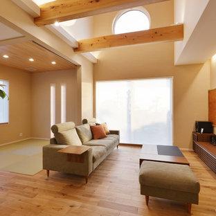 他の地域のアジアンスタイルのおしゃれなリビング (白い壁、淡色無垢フローリング、壁掛け型テレビ、ベージュの床) の写真
