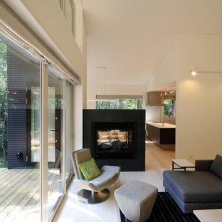 他の地域の中サイズのアジアンスタイルのおしゃれなLDK (白い壁、合板フローリング、両方向型暖炉、石材の暖炉まわり、茶色い床) の写真
