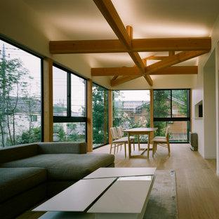 Свежая идея для дизайна: открытая гостиная комната среднего размера в стиле модернизм с белыми стенами, скрытым ТВ, бежевым полом и полом из фанеры без камина - отличное фото интерьера