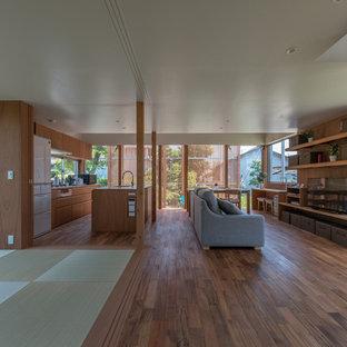 Idées déco pour un salon asiatique ouvert avec un mur marron, un téléviseur indépendant, un sol marron et un sol en bois foncé.