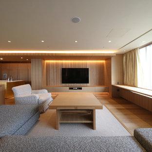 Immagine di un ampio soggiorno minimalista aperto con pareti beige, pavimento in compensato, TV a parete e pavimento beige