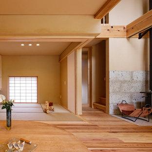 Esempio di un piccolo soggiorno moderno aperto con pareti beige, pavimento in tatami, stufa a legna, cornice del camino in pietra, TV autoportante e pavimento verde