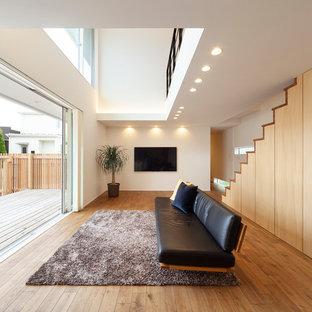 他の地域のコンテンポラリースタイルのおしゃれなリビング (白い壁、無垢フローリング、壁掛け型テレビ、茶色い床) の写真
