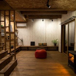 他の地域のアジアンスタイルのおしゃれなリビング (無垢フローリング、茶色い床、ベージュの壁、薪ストーブ、金属の暖炉まわり) の写真
