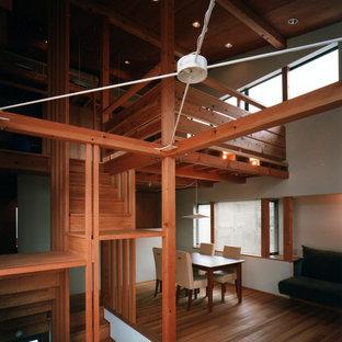 東京23区の中サイズのアジアンスタイルのおしゃれなリビング (白い壁、無垢フローリング、暖炉なし、漆喰の暖炉まわり、内蔵型テレビ、茶色い床) の写真