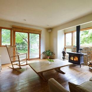 Foto de salón abierto, de estilo de casa de campo, grande, sin televisor, con paredes blancas, suelo de madera en tonos medios, estufa de leña, marco de chimenea de ladrillo y suelo beige