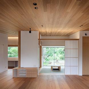 Foto de salón abierto, minimalista, de tamaño medio, con paredes blancas, suelo de madera clara, televisor independiente y suelo marrón