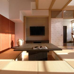 Inspiration för asiatiska vardagsrum, med vita väggar, tatamigolv, en väggmonterad TV och brunt golv