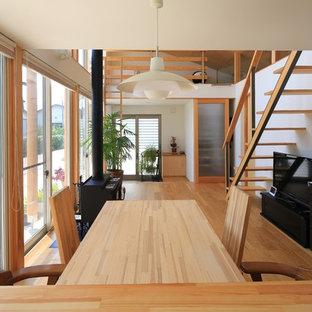 他の地域のアジアンスタイルのおしゃれなリビング (白い壁、無垢フローリング、薪ストーブ、据え置き型テレビ、ベージュの床) の写真