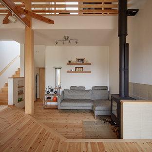 他の地域のアジアンスタイルのおしゃれなリビング (白い壁、淡色無垢フローリング、薪ストーブ、コンクリートの暖炉まわり、茶色い床) の写真