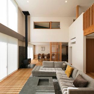 他の地域の広いコンテンポラリースタイルのおしゃれなLDK (白い壁、合板フローリング、薪ストーブ、レンガの暖炉まわり、テレビなし、ベージュの床) の写真