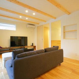 Cette image montre un salon asiatique ouvert avec une salle de réception, un mur violet, un sol en bois clair, aucune cheminée et un téléviseur indépendant.