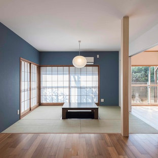 Cette image montre un salon asiatique avec un mur bleu, un sol de tatami et un sol vert.