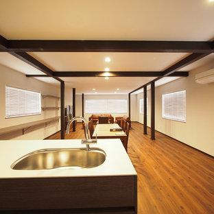 Offenes Mid-Century Wohnzimmer mit weißer Wandfarbe, Sperrholzboden, freistehendem TV und braunem Boden in Sonstige