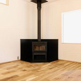 他の地域の小さい北欧スタイルのおしゃれなLDK (フォーマル、白い壁、無垢フローリング、薪ストーブ、木材の暖炉まわり、テレビなし、ベージュの床) の写真