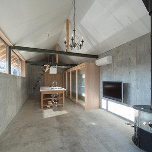 名古屋のアジアンスタイルのおしゃれなLDK (グレーの壁、コンクリートの床、薪ストーブ、コンクリートの暖炉まわり、壁掛け型テレビ、グレーの床) の写真