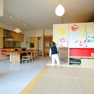 This is an example of an asian open concept living room in Tokyo with white walls, tatami floors and beige floor.