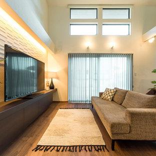 他の地域の広いモダンスタイルのおしゃれなLDK (白い壁、濃色無垢フローリング、据え置き型テレビ、茶色い床) の写真