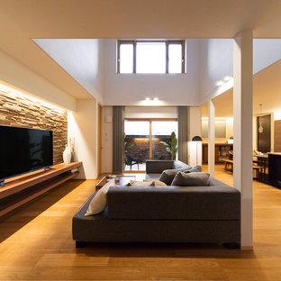 他の地域の広いミッドセンチュリースタイルのおしゃれなLDK (マルチカラーの壁、無垢フローリング、据え置き型テレビ、茶色い床) の写真