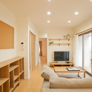 他の地域の小さいトランジショナルスタイルのおしゃれな独立型リビング (白い壁、無垢フローリング、暖炉なし、据え置き型テレビ、茶色い床) の写真