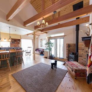 他の地域のカントリー風おしゃれなLDK (白い壁、無垢フローリング、コーナー設置型暖炉、レンガの暖炉まわり、茶色い床) の写真