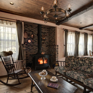 他の地域のカントリー風おしゃれなリビング (ピンクの壁、無垢フローリング、薪ストーブ、レンガの暖炉まわり、茶色い床) の写真