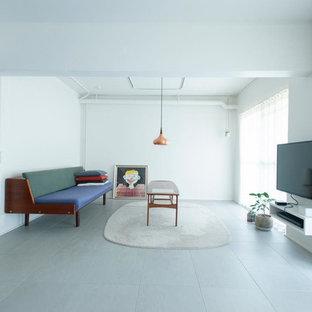 東京23区のインダストリアルスタイルのおしゃれなリビング (白い壁、壁掛け型テレビ、グレーの床) の写真