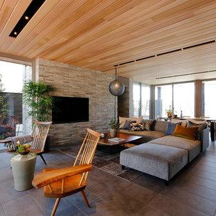 Modelo de salón abierto, minimalista, grande, sin chimenea, con paredes grises, suelo de baldosas de cerámica, televisor colgado en la pared y suelo gris