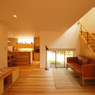 Esempio di un soggiorno moderno aperto con pareti beige e pavimento in legno massello medio