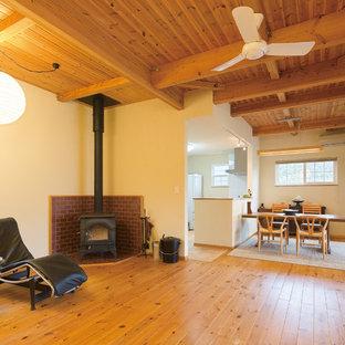 他の地域の和風のおしゃれなLDK (白い壁、無垢フローリング、薪ストーブ、レンガの暖炉まわり、茶色い床) の写真