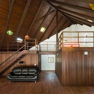 他の地域の中くらいのアジアンスタイルのおしゃれなLDK (白い壁、濃色無垢フローリング、コーナー設置型暖炉、石材の暖炉まわり、茶色い床) の写真